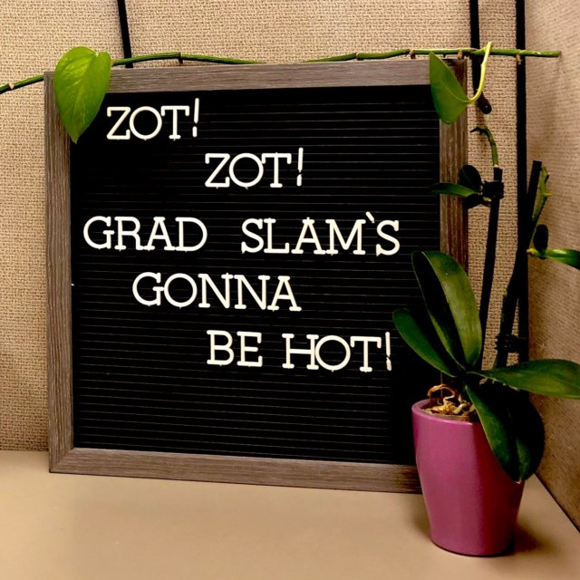 (Link to source tweet) On a shelf, between two small plants, a letterboard that says: Zot! Zot! Grad Slam's gonna be hot!